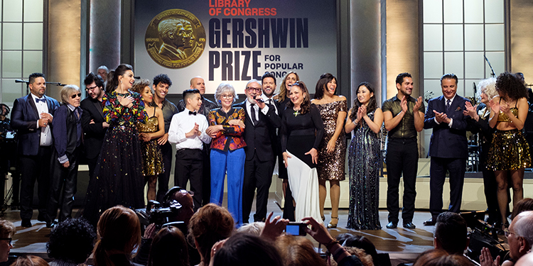 Performing artists paying tribute join Emilio, with microphone, and Gloria Estefan on stage during the finale of Emilio & Gloria Estefan: The Library of Congress Gershwin Prize for Popular Song. The concert airs on PBS at 9 pm on Friday, May 3, 2019 (chec