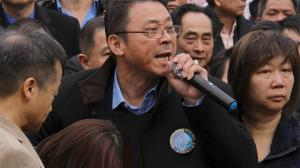 Film subject John Chan speaks at a protest in support of Peter Liang at Cadman Plaza while Peter Liang's mother bends over in distress