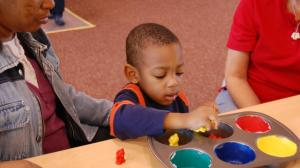 "Ready To Learn. In a Play & Learn Activity Center themed to Eric Carle's ""Brown Bear, Brown Bear, What Do You See?"", Malik Lee sorts toy bears in a muffin tin. Credit: KLRN"