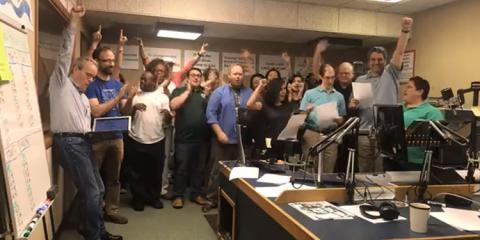 Large group of station staff celebrates and cheers when exceeding their programming goals.