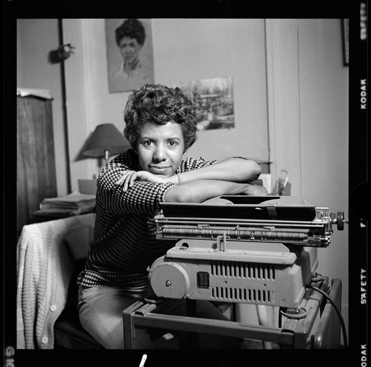Lorraine Hansberry leans over her typewriter in her Greenwich Village apartment on Bleecker Street during her April 1959 photoshoot for Vogue. Credit: David Attie