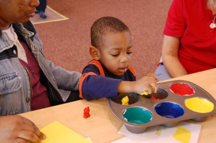 """Ready To Learn. In a Play & Learn Activity Center themed to Eric Carle's """"Brown Bear, Brown Bear, What Do You See?"""", Malik Lee sorts toy bears in a muffin tin. Credit: KLRN"""