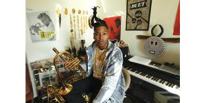 Christian Scott aTunde Adjuah sits in a room full of instruments and art.