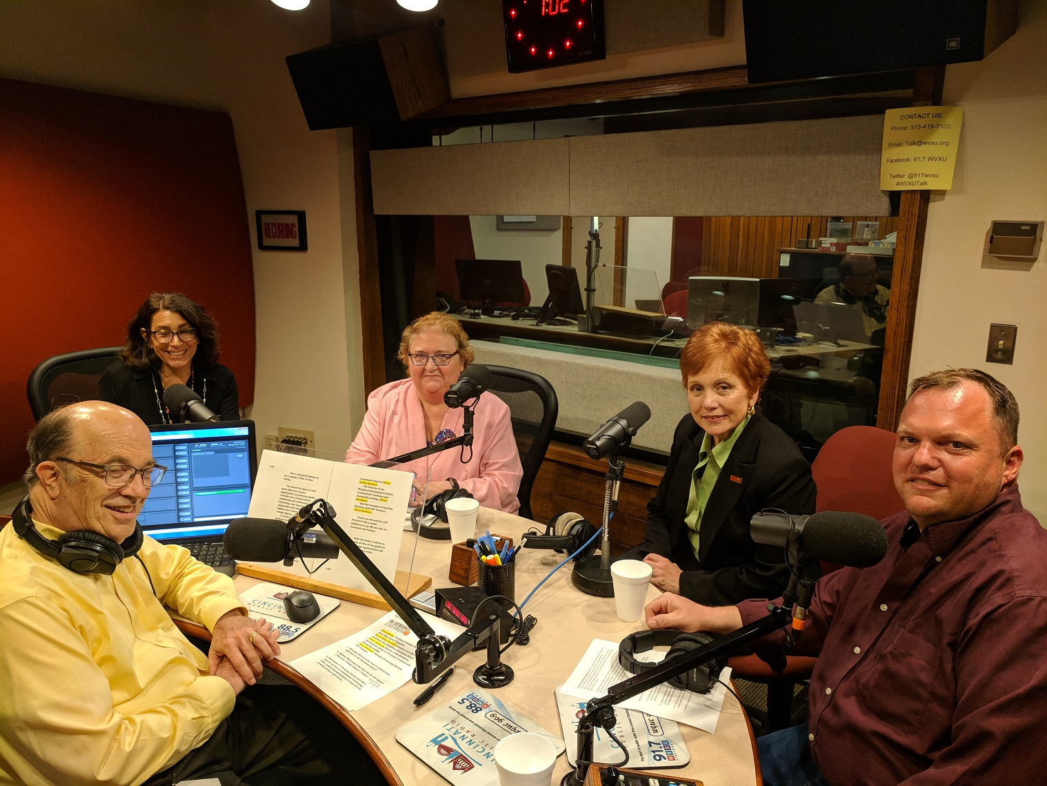 Group of four people seated around radio booth for broadcast discussion